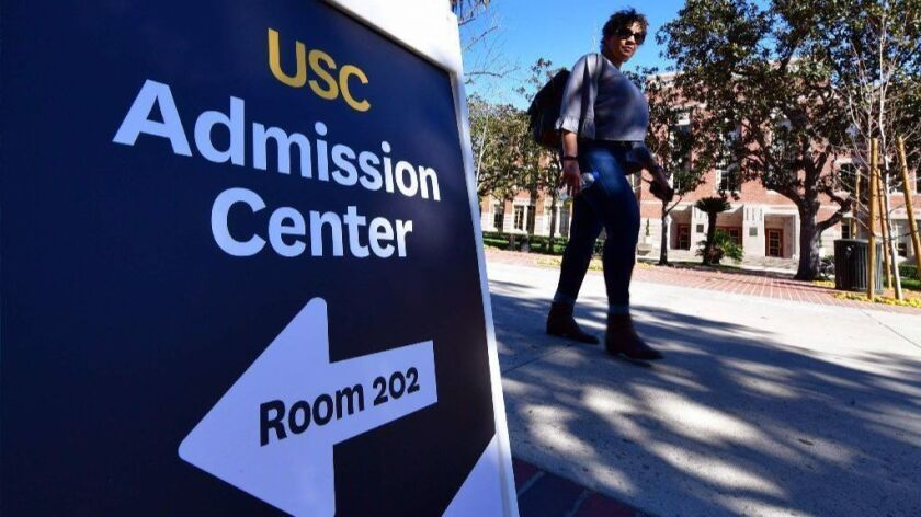 A woman walks past a sign directing people toward the admission center at USC on Wednesday.