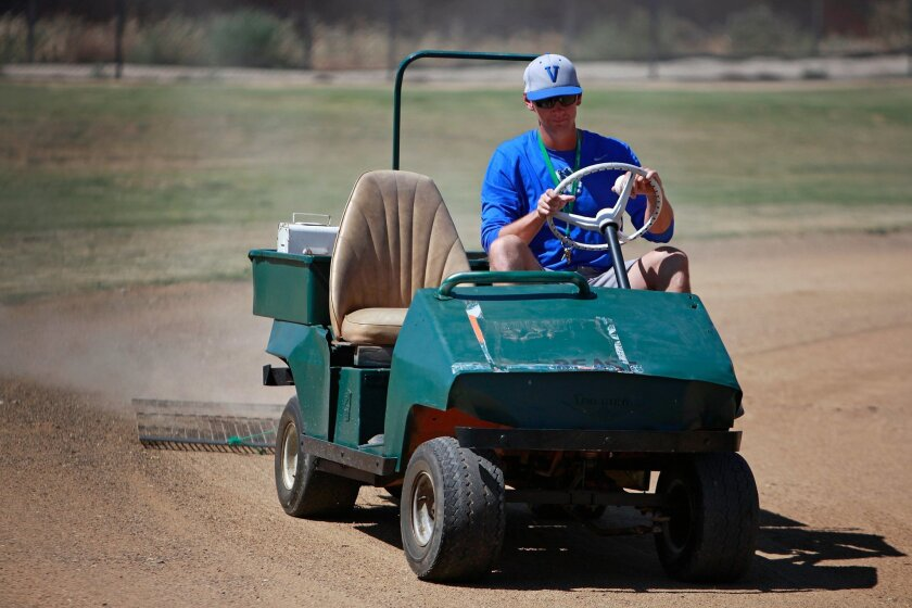 Former professional baseball player and Olympic silver medalist Adrian Burnside works on renovating the youth baseball field at the Boys & Girls club of Vista.