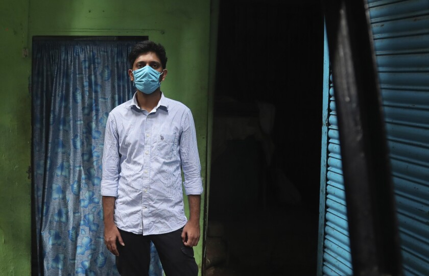 Community activist Kunal Kanase, 31, stands for a picture in a lane of Dharavi, one of Asia's largest slums, in Mumbai, India, Saturday, May 16, 2020. Kanase is among many unsung heroes working to protect some of India's most vulnerable people from the ravages of the coronavirus and the economically devastating nationwide lockdown that has left millions unable to feed themselves. (AP Photo/Rafiq Maqbool)