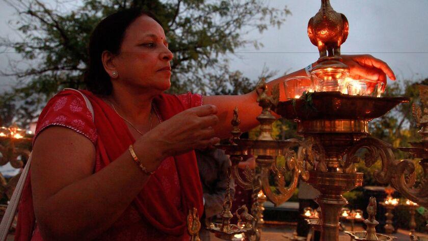Suneela Kapila lights brass lamps at dusk for the annual Festival of Lights-Diwali Celebrations last year at Balboa Park.
