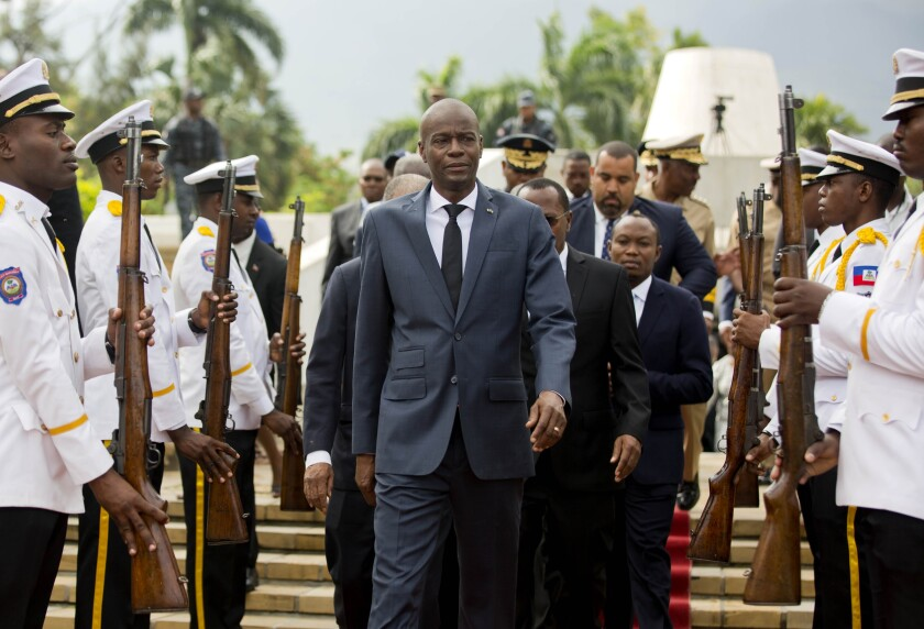 Jovenel Moïse leads a number of people through two lines of military men.