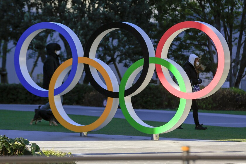 People wearing a face mask walk by the Olympic ring