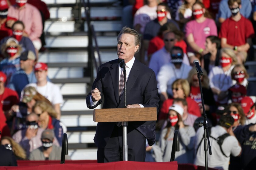 Sen. David Perdue speaks in front of a crowd at a Trump rally at Middle Georgia Regional Airport in Macon, Ga.