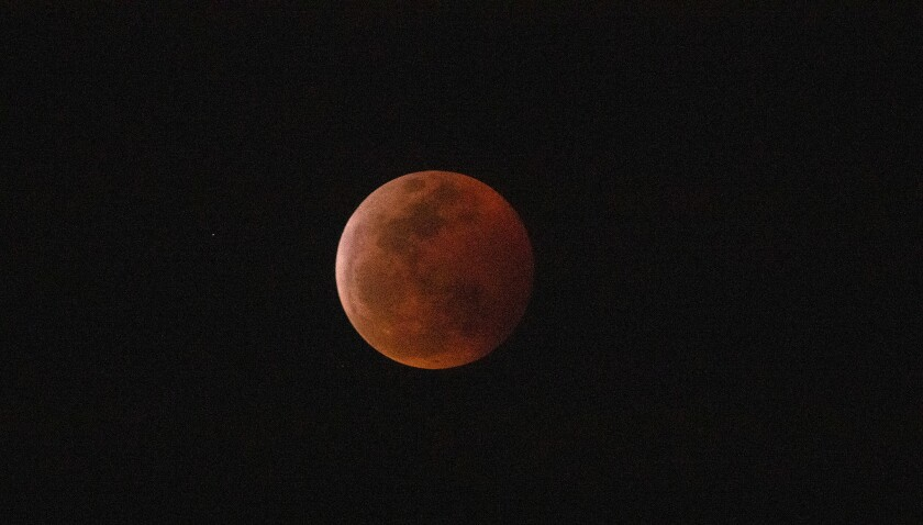 The super blood moon is engulfed into Earth's dark umbral shadow during a total lunar eclipse.