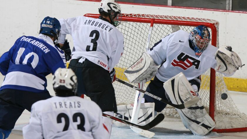 U.S. goalie Brandon Maxwell catches the puck as teammate Tyler Amburgey moves in to defend against Finland's Joonas Hurri during a 2008 tournament in Lake Placid, N.Y.
