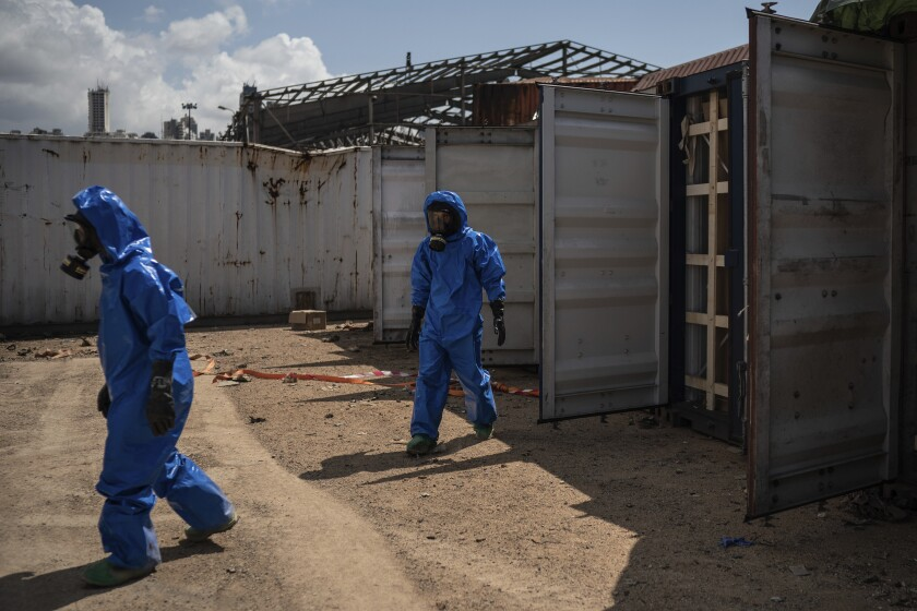 French emergency workers, part of a special unit working with chemicals, walk next to damaged containers near the site of last week's explosion, in the port of Beirut, Lebanon, Monday, Aug. 10, 2020. The unit is identifying potential leaks and securing an area where containers with flammable liquids have been damaged by the blast. (AP Photo/Felipe Dana)