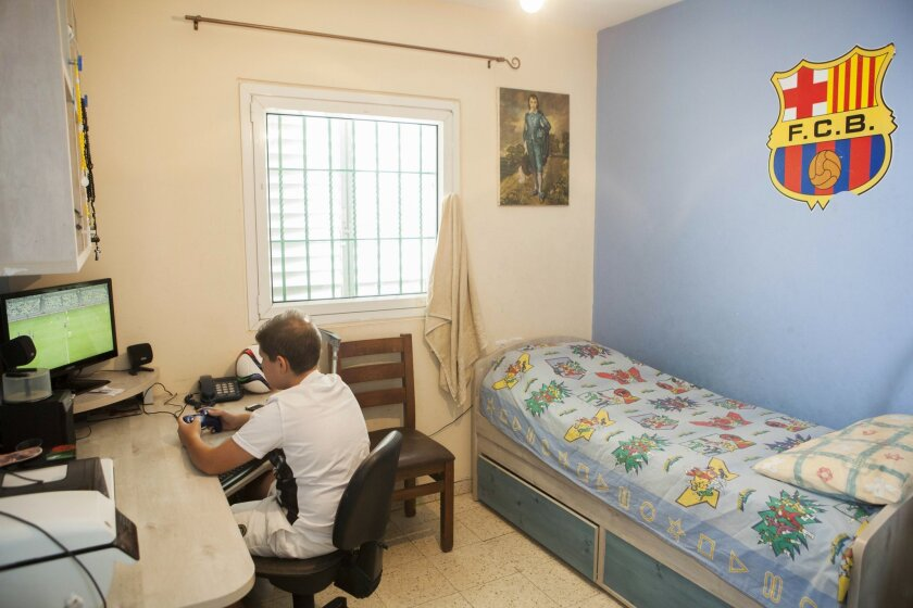 In this photo taken Tuesday, Sept. 22, 2015, Bashar Khoury plays in his room In the central Israeli city of Ramle. The Israeli school year has begun, but thousands of children from the Arab minority who attend Christian schools are still on summer vacation because of a strike to protest cuts in government funding that critics say amount to discrimination. (AP Photo/Dan Balilty)