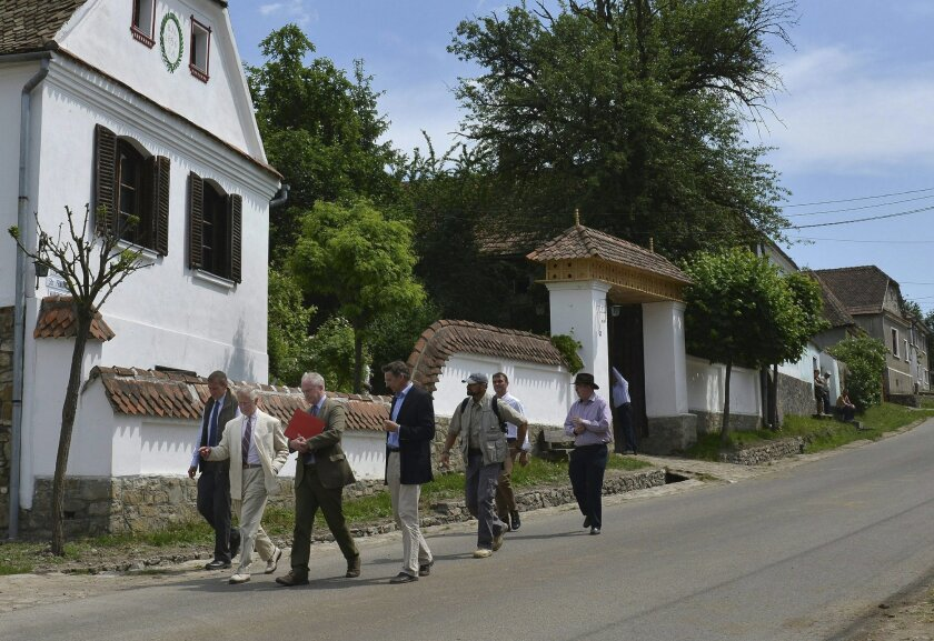 FILE - A Tuesday, June 2, 2015 photo from files of Britain's Prince Charles, second left, walking in front of the guesthouse of Hungarian Count Tibor Kalnoky, fourth left, as he tours in Miclosoara, Transylvania, Romania. Britain's Prince Charles has returned to Romania where he has a charity that