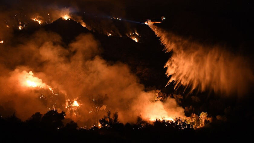 A helicopter makes a water drop on the Sand fire along Placerita Canyon Road near Santa Clarita on Sunday night.