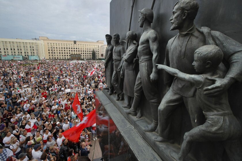 Belarusian opposition supporters gather for a protest rally in front of the government building at Independent Square in Minsk, Belarus, Tuesday, Aug. 18, 2020, with a Soviet era sculptures in the foreground. Workers at more state-controlled companies and factories took part in the strike that began the day before and has encompassed several truck and tractor factories, a huge potash factory that accounts for a fifth of the world's potash fertilizer output and is the nation's top cash earner, state television and the country's most prominent theater. (AP Photo/Dmitri Lovetsky)
