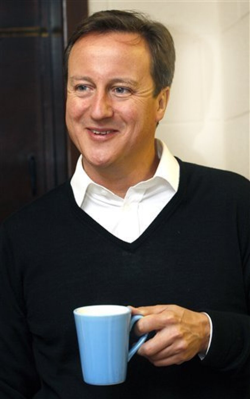 Britain's Prime Minister David Cameron drinks a cup of tea during a visit to a regeneration project at a community center in Alum Rock, in Birmingham, England, Tuesday, Oct. 5, 2010. The Conservative party is holding its annual conference at the International Convention Center in Birmingham which runs until Wednesday. (AP Photo/Kirsty Wigglesworth, pool)
