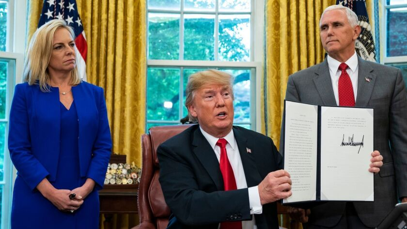 President Trump, flanked by Homeland Security Secretary Kirstjen Nielsen, left, and Vice President Mike Pence, displays the executive order he signed Wednesday reversing his own family separation policy at the border.