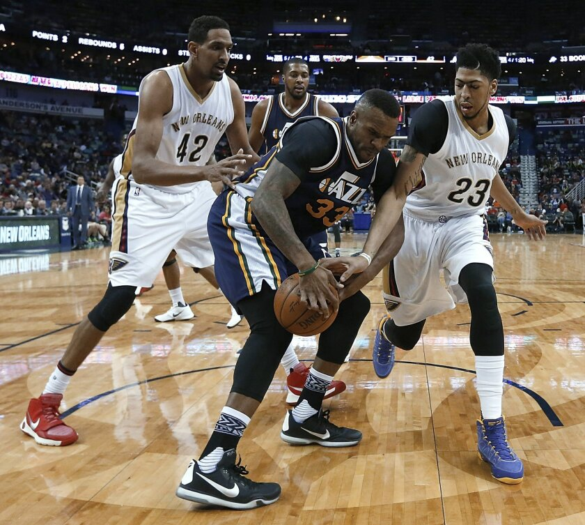 New Orleans Pelicans forward Anthony Davis attempts to strip the ball from Utah Jazz forward Trevor Booker (33) during the first half of an NBA basketball game in New Orleans, Wednesday, Feb. 10, 2016. (AP Photo/Tyler Kaufman)