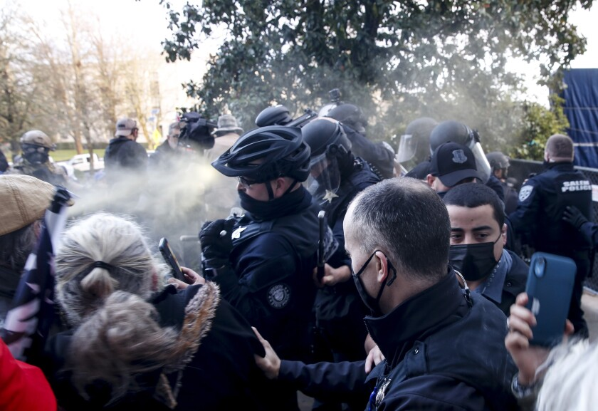Protesters spray Mace at police as they attempt to get into the Oregon State Capitol in Salem on Monday.