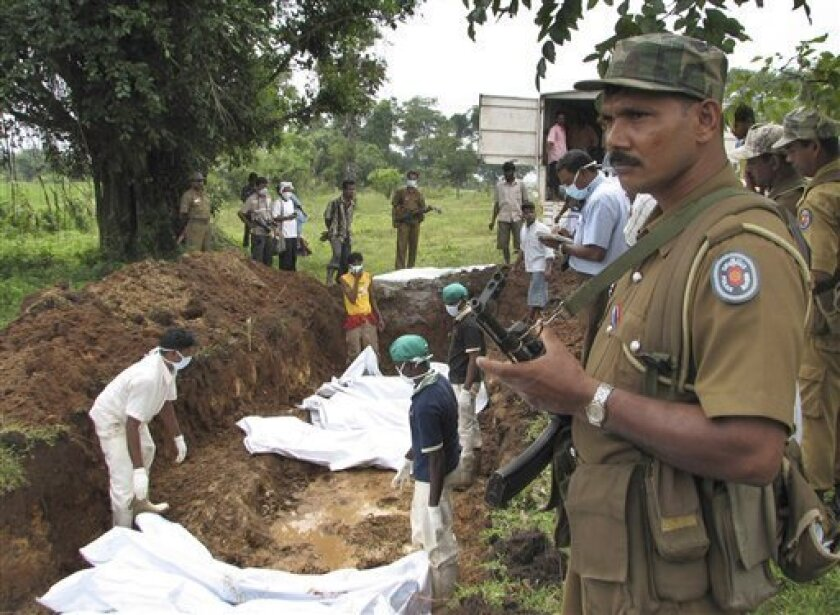 A police officer stands guard as Red Cross workers bury the bodies of Tamil rebel fighters in a cemetery in Vavuniya, about 210 kilometers (131 miles) northeast of Colombo, Sri Lanka, Wednesday, Jan. 14, 2009. Sri Lankan air force jets bombed Tamil Tiger artillery guns and key rebel positions Tuesd