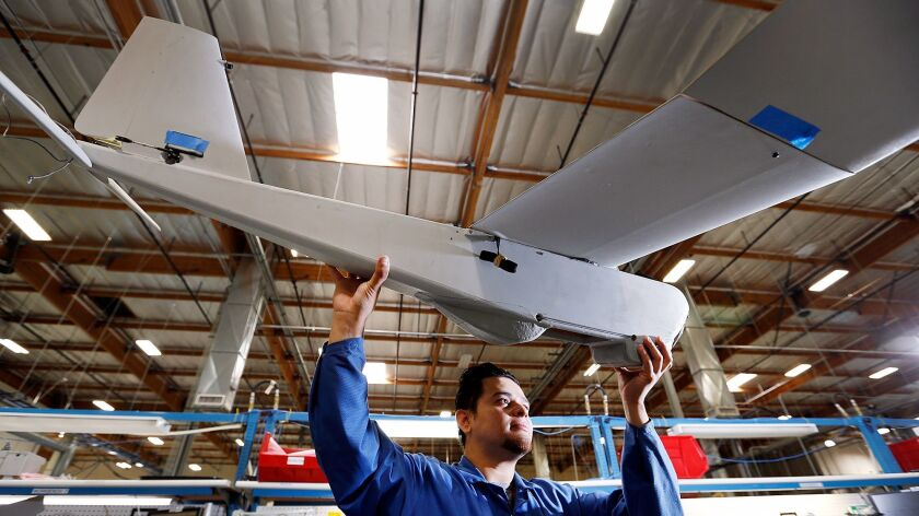 A technician at AeroVironment inspects parts of an unmanned aircraft in 2015.