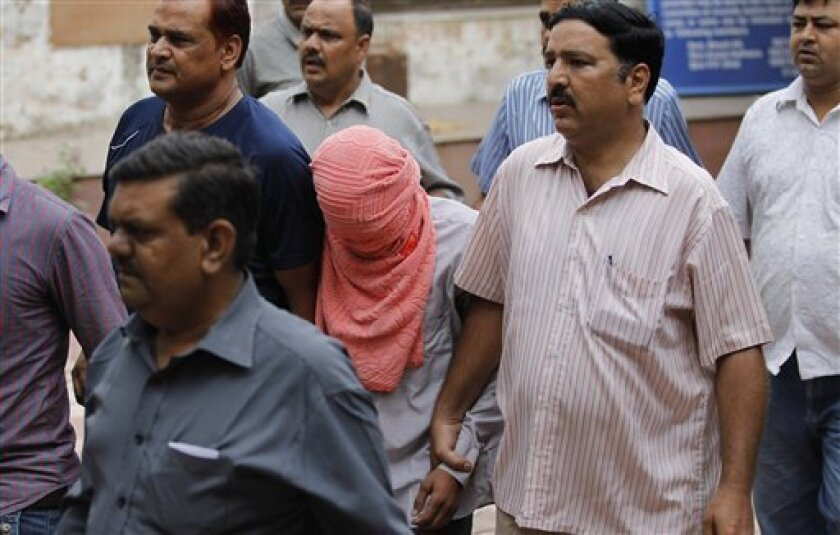 Delhi police officers escort  a juvenile accused of rape, outside the Juvenile justice board in New Delhi, India, Saturday, Aug. 31, 2013. An Indian juvenile court on Saturday handed down the first conviction in the fatal gang rape of a young woman on a moving New Delhi bus, convicting the teenager