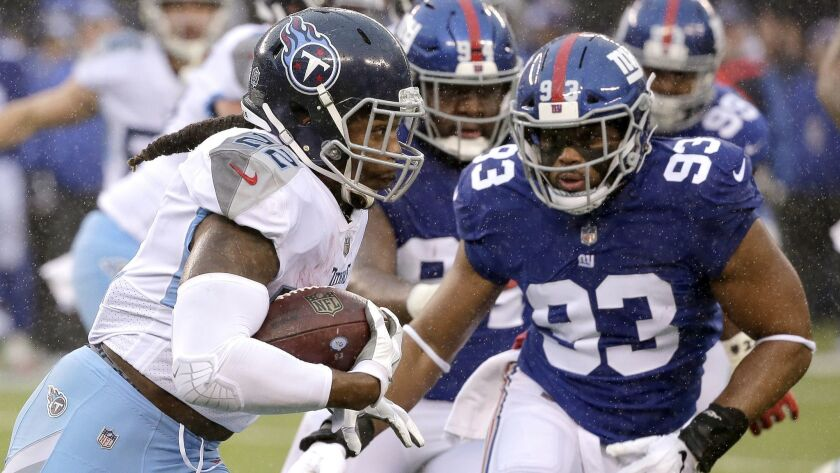 Tennessee Titans running back Derrick Henry, left, runs with the ball as New York Giants middle line