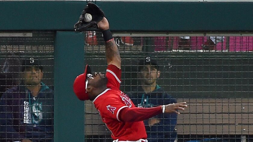 Angels outfielder Eric Young Jr. makes a leaping catch at the bullpen fence on a fly ball by the Seattle Mariners' Robinson Cano in the third inning on Friday.