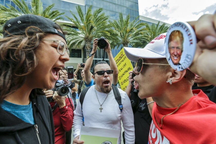 Donald Trump supporter Jake Towe, right, faces off with Trump protester Joshua Gonzalez, left, outside the Anaheim Convention Center during a Trump rally Wednesday, May 25, 2016.