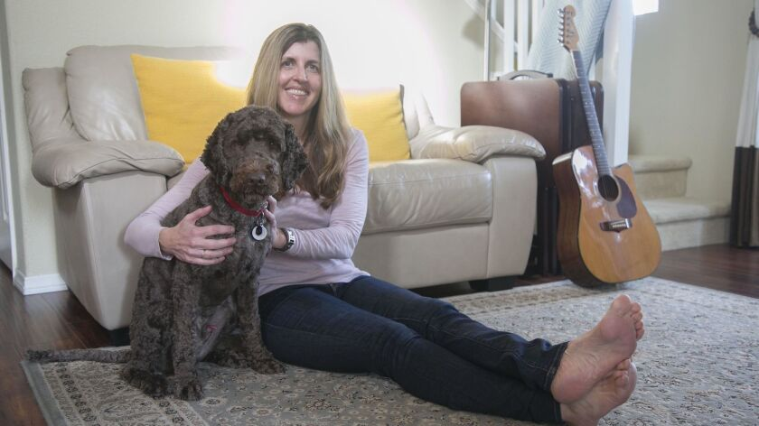 """Author Susan Hannifin-MacNab and her therapy dog, Kai, relax at her home in Carmel Mountain Ranch. She got Kai after she lost her husband to a vehicle accident at a young age. She has written a book, """"A to Z Healing Toolbox,"""" to help others work through grief and trauma issues."""