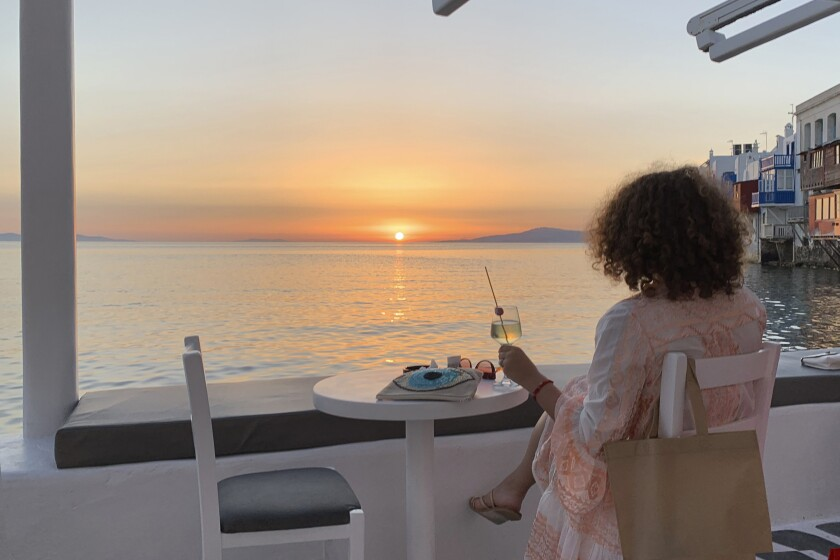 In this Tuesday, June 9, 2020 photo, a visitor watches the sunset at a bar in an area known as Little Venice in the main town of the island of Mykonos, Greece. Business owners and locals officials on the Greek holiday island of Mykonos, a popular vacation spot for celebrities, club-goers, and high rollers, say they are keen to reopen for business despite the risks of COVID-19 posed by international travel. Greece will official launch its tourism season Monday, June 15, 2020 after keeping the country's infection rate low. (AP Photo/Derek Gatopoulos)