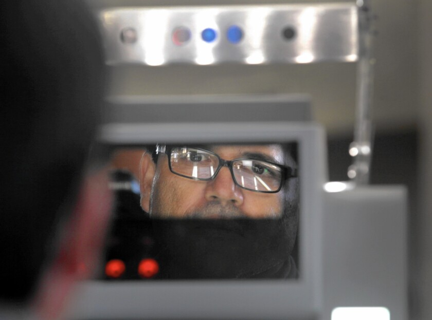 A man stands before a biometric machine being tested at the Otay Mesa port of entry. The system scans the face and irises and records the information, which will be used to track non-U.S. citizens who travel across the border.