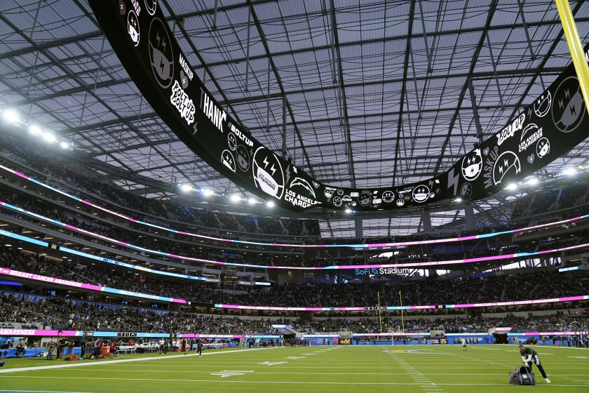 Players leave the field at SoFi Stadium during a weather delay shortly before the scheduled start of an NFL football game between the Los Angeles Chargers and the Las Vegas Raiders, Monday, Oct. 4, 2021, in Inglewood, Calif. (AP Photo/Marcio Jose Sanchez)