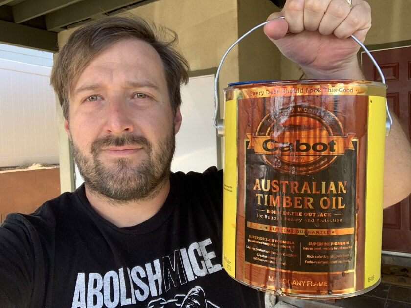 """Ryan Bradford and his can of """"Mahogany Flame"""" paint."""