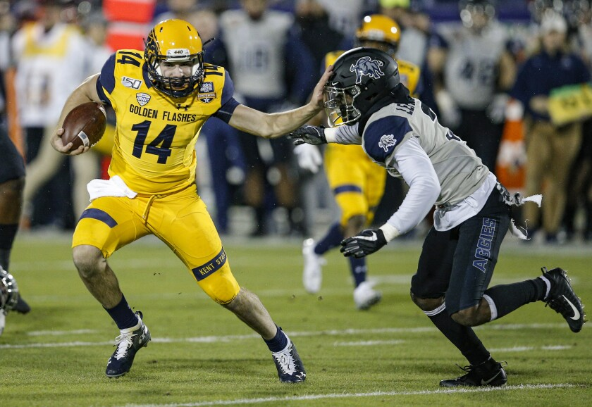Kent State quarterback Dustin Crum carries the ball as Utah State safety Troy Lefeged Jr. defends in the Frisco Bowl.