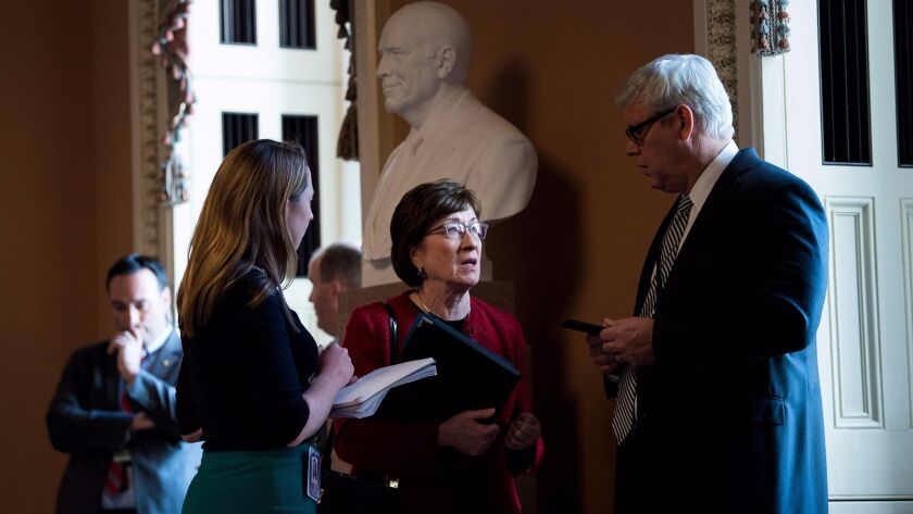 Sen. Susan Collins (R-Maine) speaks with staff before attending a meeting with other Republicans on Capitol Hill on Wednesday.