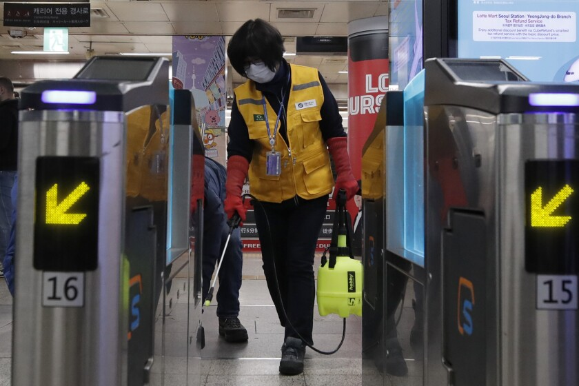 A worker sprays disinfectant as a precaution against the new coronavirus at a Seoul subway station on Wednesday.