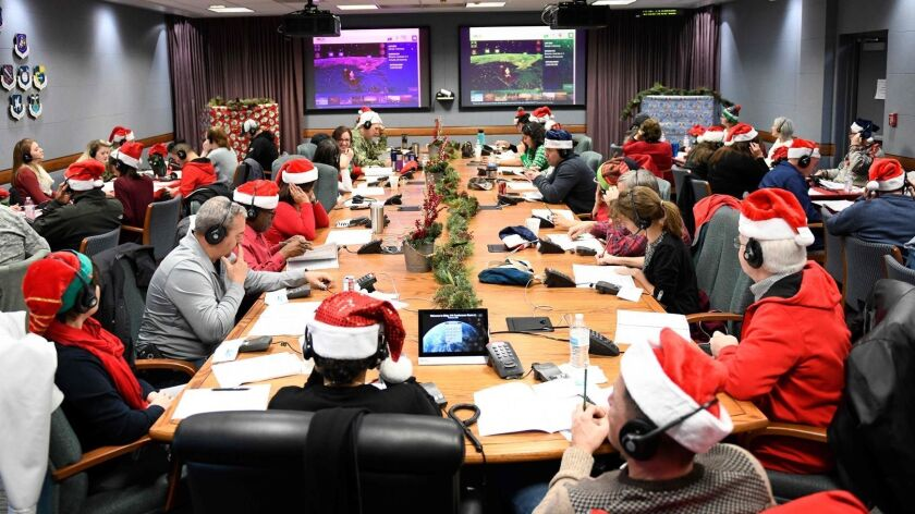 Volunteers work at the 2018 NORAD Tracks Santa Operation Center at Peterson Air Force Base in Colorado Springs, Colo.