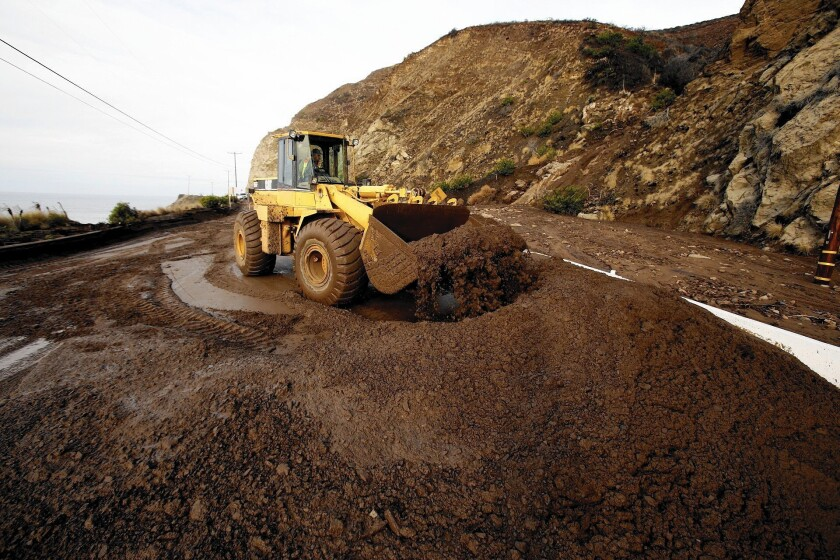 Work crews remove mud and debris from a mudflow that closed Pacific Coast Highway between Las Posas and Yerba Buena roads in Ventura County in December 2014.