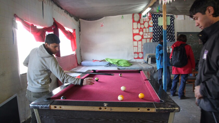 Boys play pool in the Jungle Books Kids Cafe. The cafe has provided a place where young people in the Calais refugee camp can listen to music, play games, eat warm food and charge their cellphones.