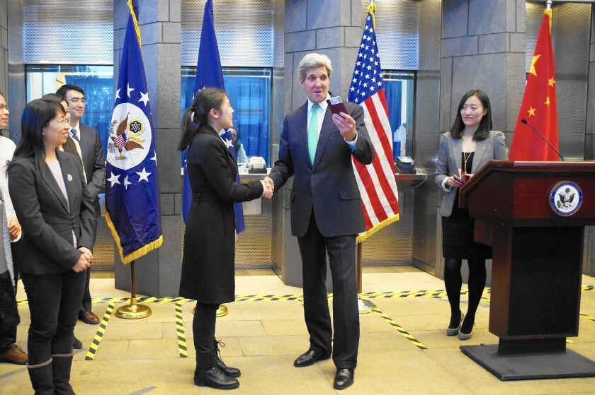 U.S. Secretary of State John Kerry prepares to give a visa to a Chinese woman at a press conference at the U.S. Embassy in Beijing.