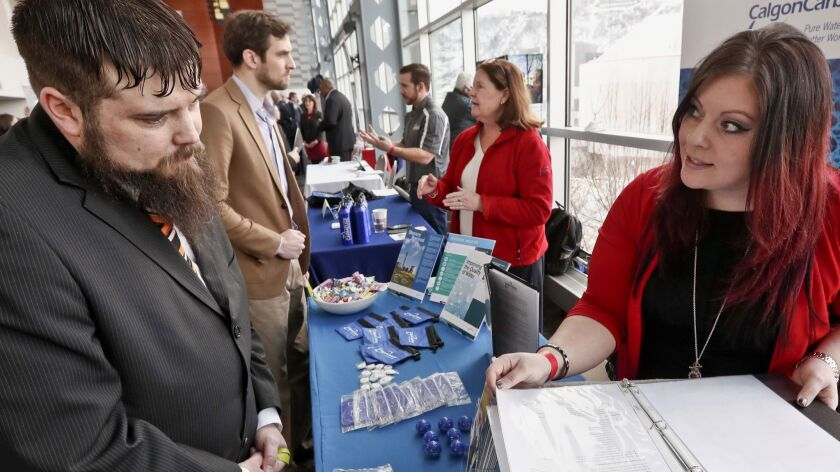 FILE - In this March 7, 2019, file photo visitors to the Pittsburgh veterans job fair meet with recr