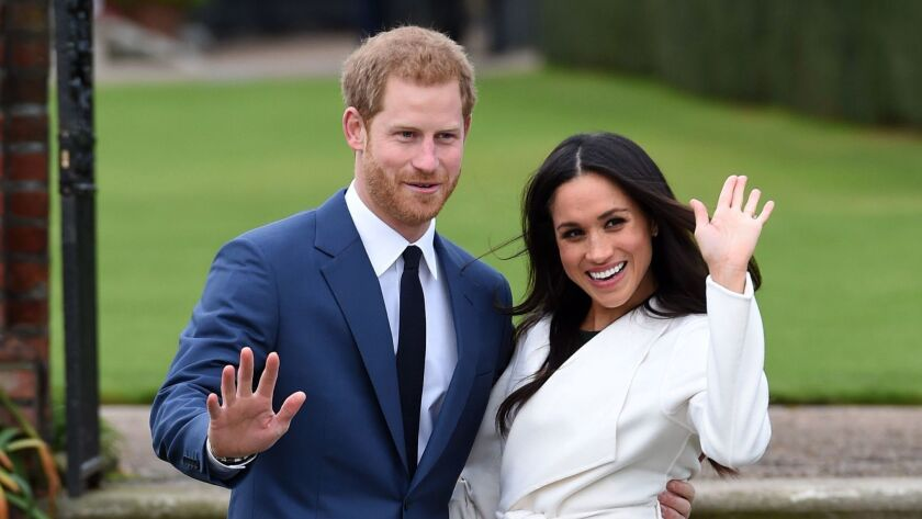 Britain's Prince Harry and Meghan Markle pose for the media in the grounds of Kensington Palace in L
