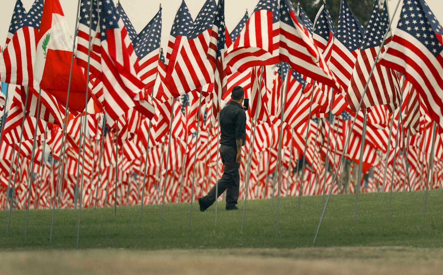MALIBU, CA - SEPTEMBER 10: Rich Smith for his first time viewing the flags on Thursday as Pepperdine University for the 13th year is commemorating the lives lost in the terror attacks on September 11, 2001, with the Waves of Flags display at Alumni Park on the Malibu campus. In compliance with guidance provided by Los Angeles County due to the COVID-19 pandemic, the display will be closed to the public but spectators can view the display from the public sidewalk adjacent two the park. The installation commemorates the 2,977 lives lost in the terror attacks of September 11, 2001, featuring a vast display of American flags as well as international flags representing the home countries of those from abroad. Pepperdine University on Thursday, Sept. 10, 2020 in Malibu, CA. (Al Seib / Los Angeles Times