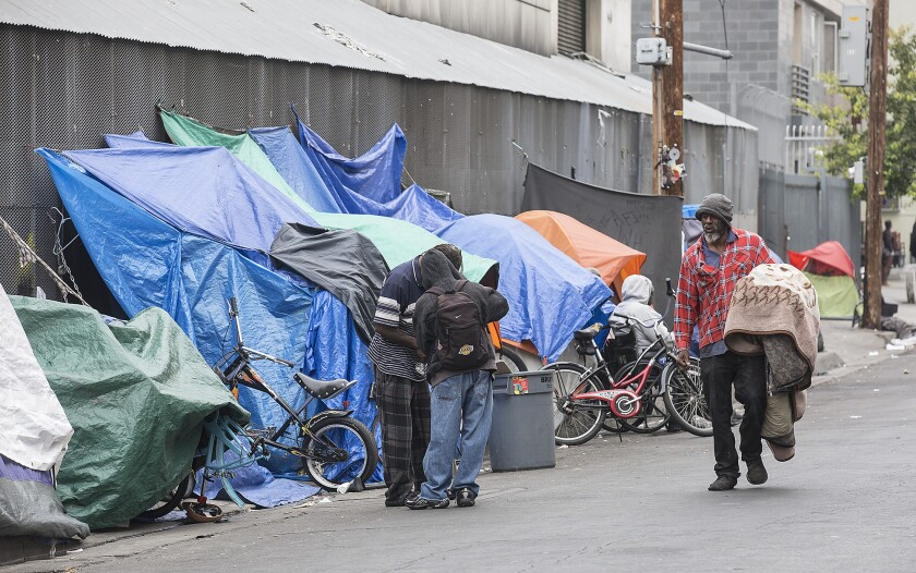 Homeless people set up tarps and tents in downtown Los Angeles' skid row.