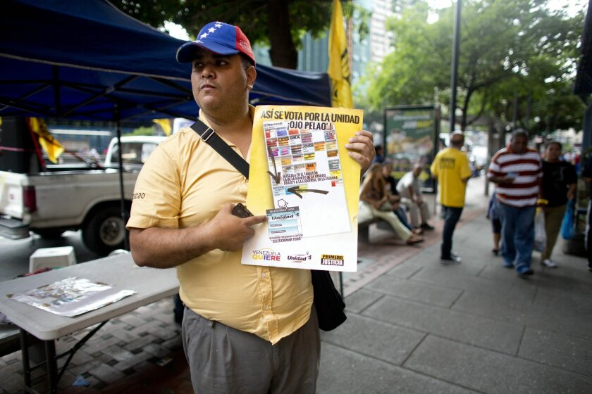 An activist of the opposition Primero Justicia or Justice First political party, holds a poster showing how to vote in the next congressional elections, in Caracas, Venezuela, Thursday, Nov. 26, 2015. An opposition leader was shot to death Wednesday while campaigning for next week's congressional elections in Venezuela, members of his political party said. The shooting took place in the central town of Altagracia de Orituco, said the leader of the Democratic Action Party, Carolos Prosperi. He said he heard gunshots as the rally was breaking up and the town's party leader Luis Manuel Diaz, was hit. (AP Photo/Ariana Cubillos)