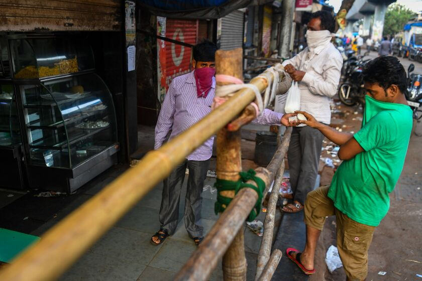 A tea seller hands cups to a customer from behind a barricade to preserve social distancing inside the Dharavi slum of Mumbai, India.