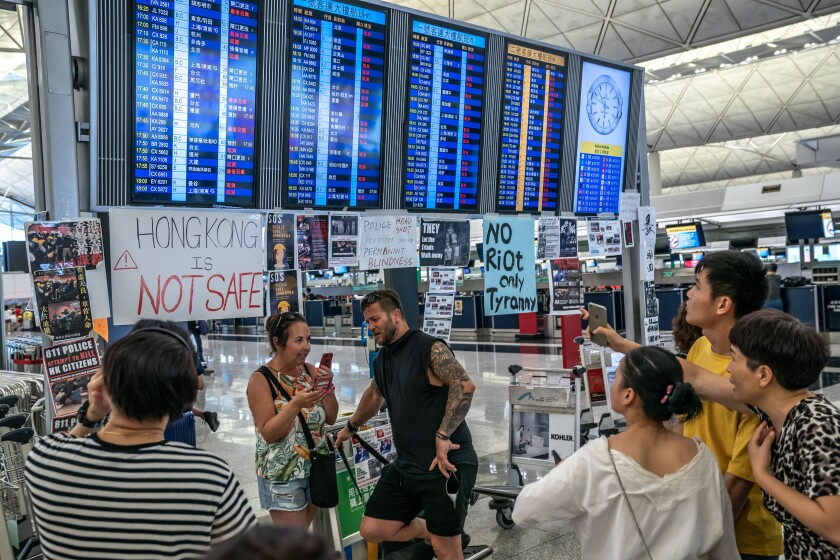 Tourists look at the information panel at the Hong Kong International Airport during a demonstration.