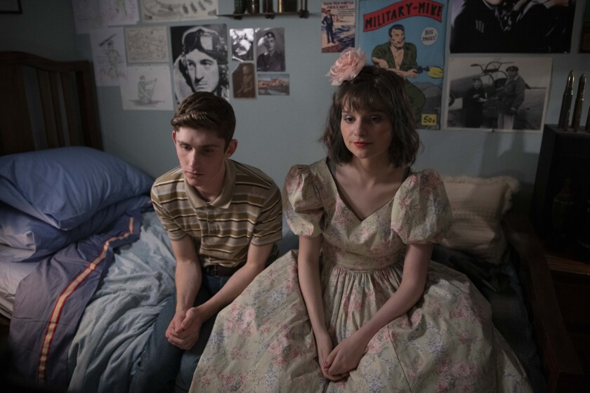 A teenage boy and girl sitting on a bed