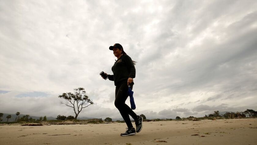 CARPENTER CA MAY 6, 2019 -- Lucy Macias vacationing from Mexico at Carpenteria State Beach jogs bet