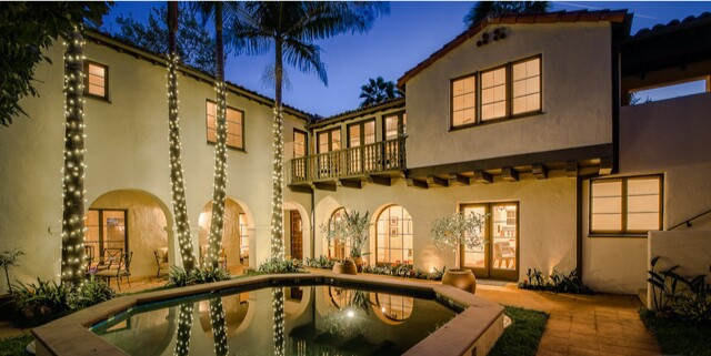 Built in 1929, the Spanish-style home opens to a romantic courtyard with palm trees and a pool.