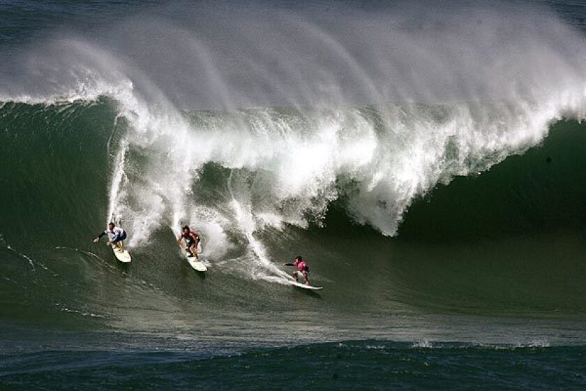 Noah Johnson, Kohl Christensen and Ibon Amatrian ride a wave during a big wave surfing contest at Waimea, Hawaii.
