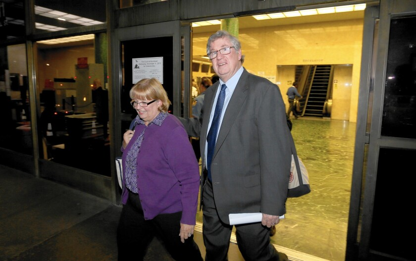 Former Times sports columnist T.J. Simers and his wife, Ginny, leave an L.A. courthouse Wednesday after he won a discrimation case against the newspaper.
