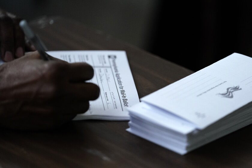 A person fills out an application for a mail-in ballot before voting.