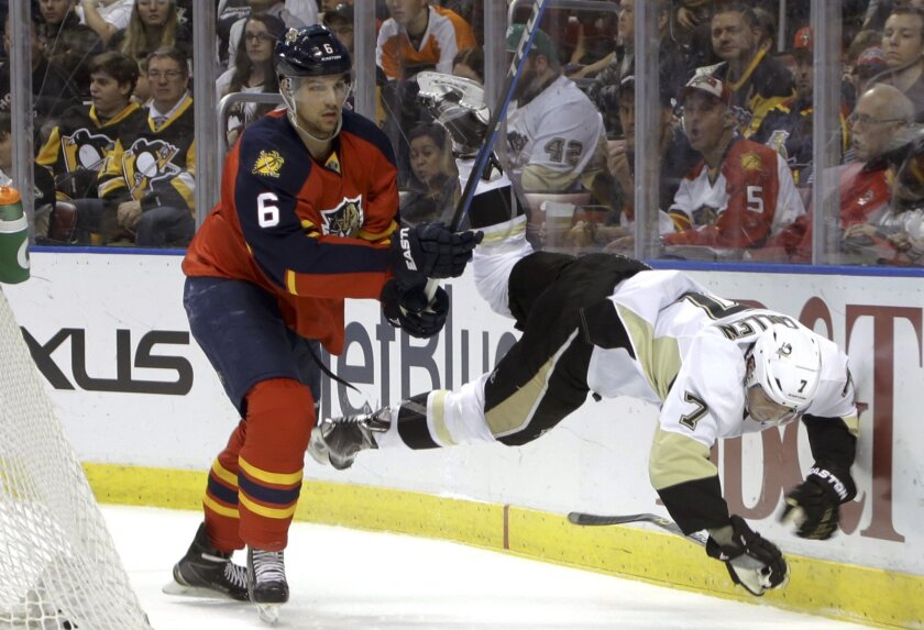 Pittsburgh Penguins center Matt Cullen (7) flies off the ice as he goes for the puck against Florida Panthers defenseman Alex Petrovic (6) during the first period of an NHL hockey game, Saturday, Feb. 6, 2016, in Sunrise, Fla. (AP Photo/Lynne Sladky)